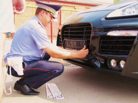 Сотрудник ГАИ снимает номера с Porsche Cayenne