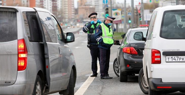 На фото - сотрудники ГИБДД проверяют пропуски у водителей